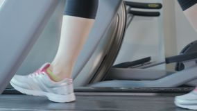 Run on the treadmill. Close-up. The camera moves from the right to the left. Young woman wearing sporty sneakers is in the gym. Sporty young woman is at the stock video
