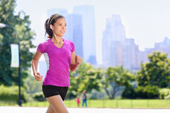 Run woman exercising in Central Park New York City. With urban background of skyscrapers skyline. Active Asian female runner running with purple t-shirt and royalty free stock photo