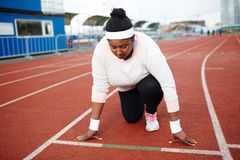 Before run. Young overweight woman standing by start line on racetrack ready to run Royalty Free Stock Photo