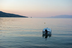 Runabout Boat Moored in Bay, Dawn. Runabout boat with outboard motor moored in Gulf of Corinth bay, calm water, Greece, at dawn with pink pre sunrise light Royalty Free Stock Photo