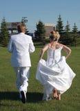 Runaway. Bride and groom running away Stock Photography
