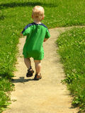 Runaway boy. A one year old toddler boy runs down a path Royalty Free Stock Image