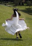 Runaway Bride 1. A bride runs away in training shoes Stock Image