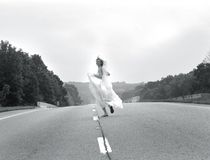 Runaway Bride. Bride laughs as she runs down a highway holding her gown.  Black and white photo Royalty Free Stock Image