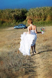 Runaway bride. Going to the car Royalty Free Stock Photography