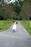 Runaway Bride. A beautiful redheaded bride running away, or rushing late Stock Photography