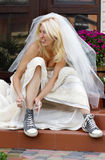 Runaway bride. Beautiful smiling bride sitting on the porch and putting on old blue trainers Royalty Free Stock Photos