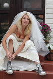 Runaway bride. Beautiful smiling bride sitting on the porch and putting on old blue trainers Stock Photo