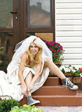 Runaway bride. Beautiful smiling bride sitting on the porch and putting on old blue trainers Stock Photos