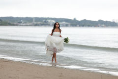 Runaway bride. On a beach Royalty Free Stock Image