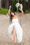 Runaway bride. Sitting on a swing Stock Photo