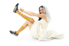 Runaway bride. Beautiful smiling bride sitting on the floor and putting on old blue trainers Royalty Free Stock Photo