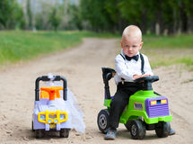 Runaway bride. Sad baby boy at his toy car, another car beside is empty Stock Photo