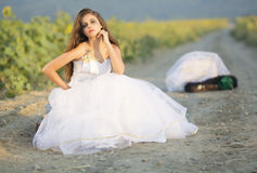 Runaway bride. Bride wearing a white wedding gown on the country road Royalty Free Stock Photo