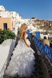 Runaway bride in a wedding dress in Santorini in Greece. Beautiful blond runaway bride in white wedding dress fabulous with a very long train of crystals in the Royalty Free Stock Images