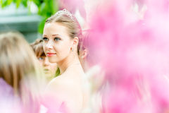 Runaway Brides Cosmopolitan, Moscow, 2013. MOSCOW, RUSSIA - 25 MAY: Runaway Brides Cosmopolitan took place in Ermitage Garden. Bride through the blurred flowers Royalty Free Stock Photography