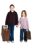 Runaway sisters. Sisters handing hand with vintage suitcases Stock Images