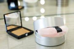 Rund ask med pulver och den rosa pälssvampen och rouge i en fyrkantig ask i en skönhetsalong royaltyfri foto