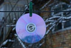 Rund CD-SKIVA som hänger på tråd på klädnypa Fotografering för Bildbyråer