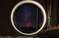 Rund cirkelfönsterram med natthimmel mycket av stjärnor med den mjölkaktiga vägen Royaltyfri Foto