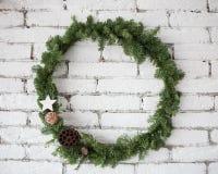 Rund elegant julkrans som hänger på den vita tegelstenväggen Royaltyfria Bilder
