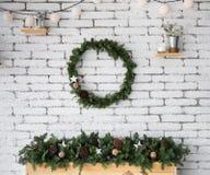 Rund elegant julkrans som hänger på den vita tegelstenväggen Royaltyfri Fotografi