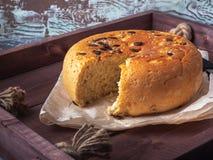 Rund-förmiges selbst gemachtes Brot mit Samen in einem Schnitt auf einem hölzernen rustikalen Behälter, nahe bei ihm ist ein Küch lizenzfreie stockfotos