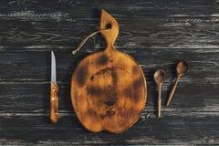 Rund gammal skärbräda med en träsked och en kniv på en mörk lantlig bakgrund ovanför sikt arkivbilder
