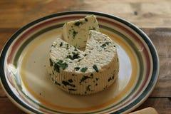 Rund hemlagad ny naturlig ost som ligger på en platta på en trätabell royaltyfria foton
