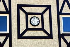 Rund klocka på den gråa väggen av byggnaden Arkivfoto