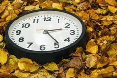 Rund klocka som ligger på höstsidor Royaltyfri Fotografi