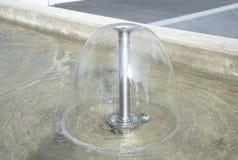 Rund liten springbrunn med vatten som går ner i dammet arkivbilder