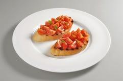 Rund maträtt med grillad bröd- och tomatbruschetta royaltyfri foto