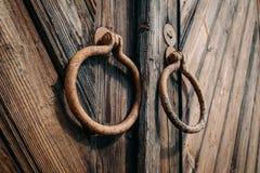 Rund metall behandlar på den stängd gammal antik träporten eller dörr royaltyfria foton