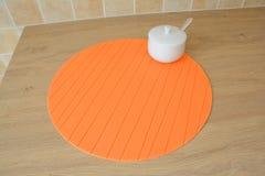 Rund orange tablemat- och sockerbunke på tabellen Royaltyfri Foto