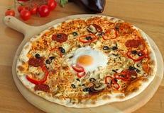 Rund pizza med ett ägg på ett träbräde Fotografering för Bildbyråer