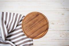 Rund pizzaskärbräda och randig bordduk på vit träbakgrund Top beskådar Kopieringsutrymme och åtlöje upp fotografering för bildbyråer