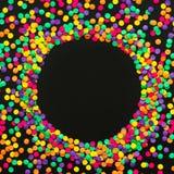Rund ram av mångfärgade konfettier på svart bakgrund royaltyfri bild