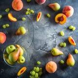 Rund ram av persikor, päron och druvor på mörk bakgrund Skivade persikor på den mörka tabellen Fruktbegrepp Lekmanna- lägenhet, b Royaltyfria Bilder