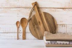 Rund skärbräda för trä, skedar, bunt av linnekökshanddukar på vit plankaträbakgrund arkivbild