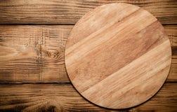 Rund skärbräda på den gamla träbrända tabellen eller bräde för baksida Arkivbilder