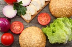 Rund smörgåsbulle med, tomat, röd lök, grön grönsallat, grillad feg filé på träbakgrund Arkivfoto