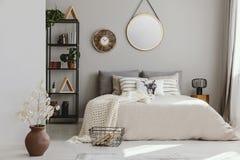Rund spegel och klocka ovanför säng med kuddar i det ljusa sovrummet som är inre med blommor royaltyfria foton