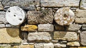 Rund sten och gammal sten i den forntida väggen royaltyfria bilder