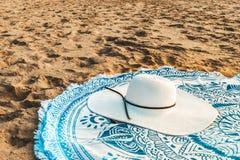 Rund strandhandduk och White Hat i sommar arkivbilder