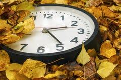 Rund svart klocka som ligger på orange höstsidor arkivbild