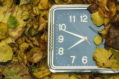 Rund svart klocka som ligger på orange höstsidor fotografering för bildbyråer