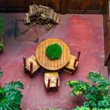 Rund tabell med tre stolar i den inre borggården av ett gammalt Europé-stil porthus royaltyfria foton