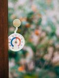 Rund termometer på fönstret 5 grader celsiust Snön ut Arkivbilder
