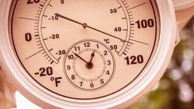 Rund termometerklocka som visar över 110 grader Arkivbilder